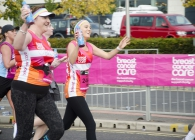 Some ladies running wearing breast cancer care vests