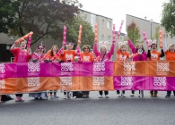 a group of supporters standing behind a barrier wearing breast cancer care tshirts and waving banners