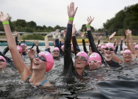Swimmers in a lake with pink hats