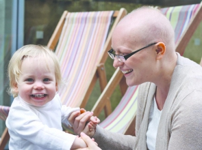 A woman with hair loss due to breast cancer treatment holds her baby