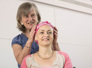 A Breast Cancer Care support volunteer helps a woman try on a headscarf