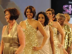 Three women in gold dresses on a catwalk